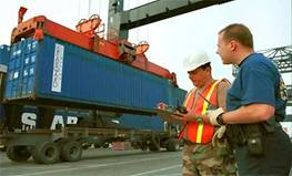 U.S. Customs inspector and National Guardsman accounting for each container as they are removed from a ship.